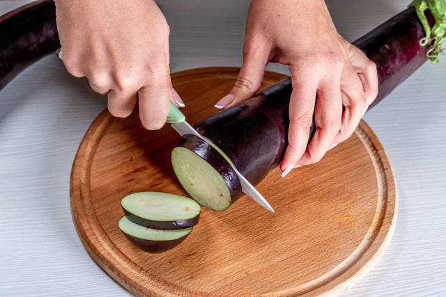 A woman cuts an eggplant with a knife on the kitchen Board
