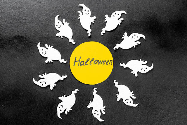 Inscription Halloween on a yellow circle with white ghosts around on a black background