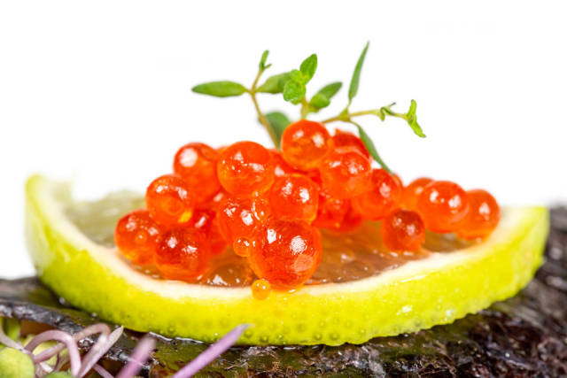 Close-up, red caviar on lime slices with thyme