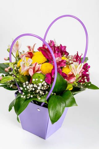 Flower arrangement in a gift box on white