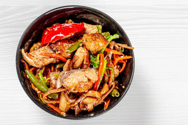 Japanese buckwheat noodle soba with vegetables, diced tuna, sauce and mushrooms in white bowl. Top view