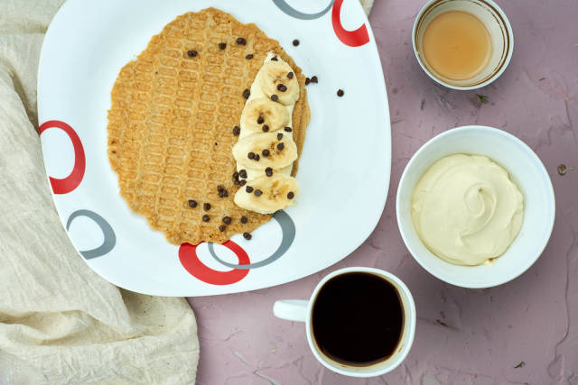 Gluten-free banana oat waffles with bowl of cream, honey and coffee cup