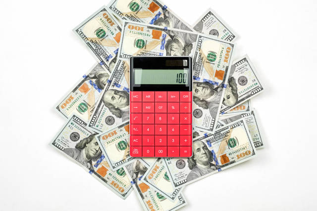 A calculator placed on the pile of US dollars