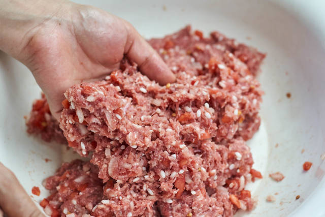 Woman stirring minced meat with rice