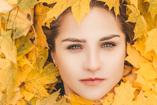 Close-up of a girls face surrounded by yellow maple leaves