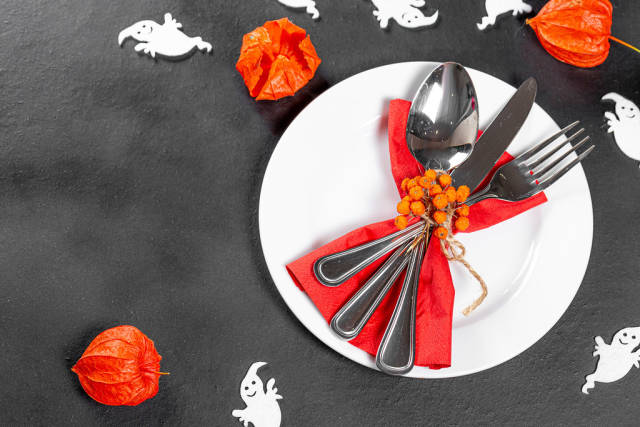 Cutlery on a black background with white ghosts and fruits of physalis. Table setting for Halloween