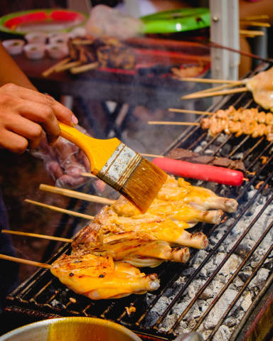 Persons hand brushing oil on a chicken barbecue