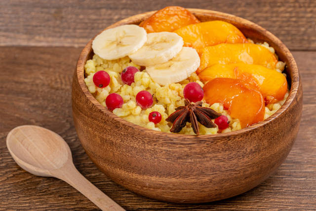 Breakfast porridge concept with peach, banana and currant in wooden bowl