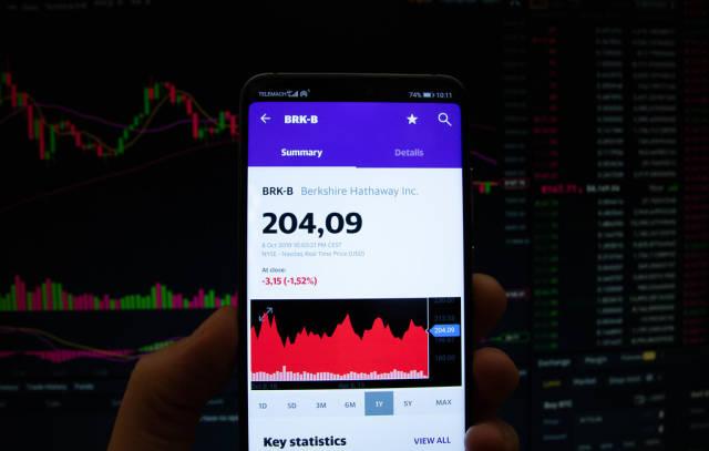 A smartphone displays the Berkshire Hathaway Inc. market value