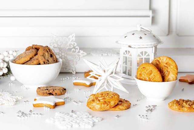 Christmas background with different cookies, decor and lantern with burning candles