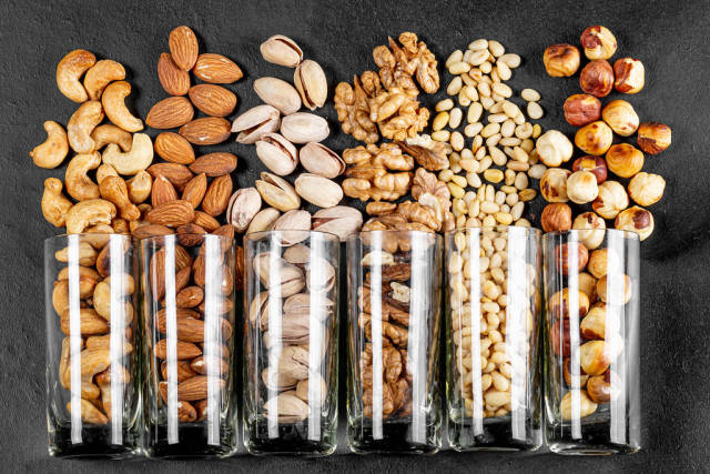 Top view, glasses with pistachios, almonds, cashews, walnuts, pine nuts and hazelnuts on a black background