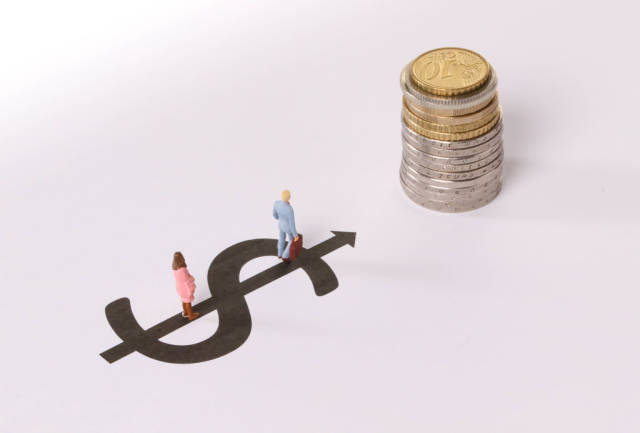 Man and Woman standing on dollar symbol pointing at stack of coins