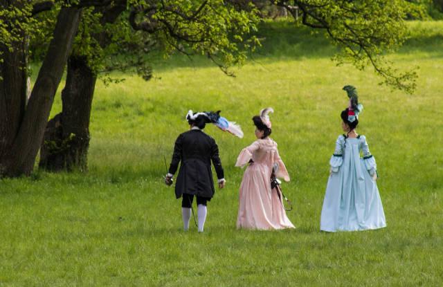 People in baroque costumes walking in park