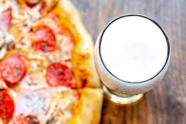 Ansicht von oben auf ein gefülltes Bierglas mit hellem Bier und Schaumkrone, neben einer runden Pizza auf einer rustikalen Holzoberfläche