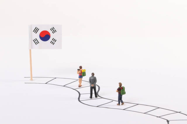 Miniature people walking on a path to the flag of South Korea