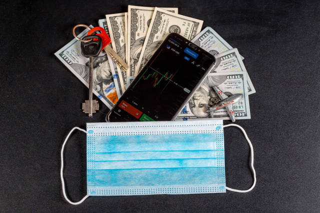 Medical mask with cash and smartphone on black background