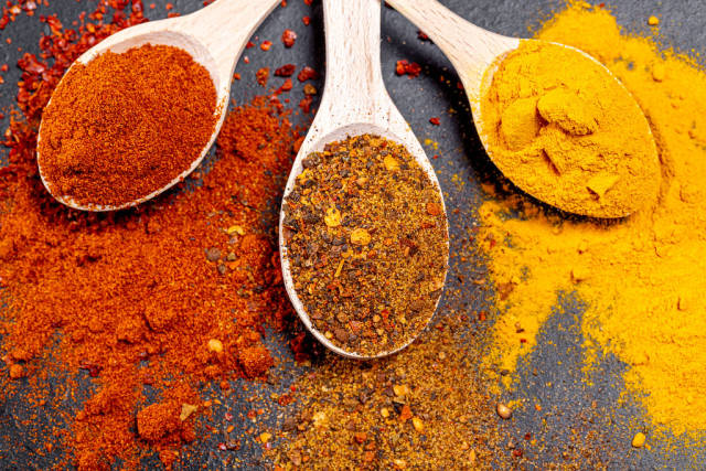 Fragrant spices. Ground paprika, turmeric and a mixture of peppers in wooden spoons