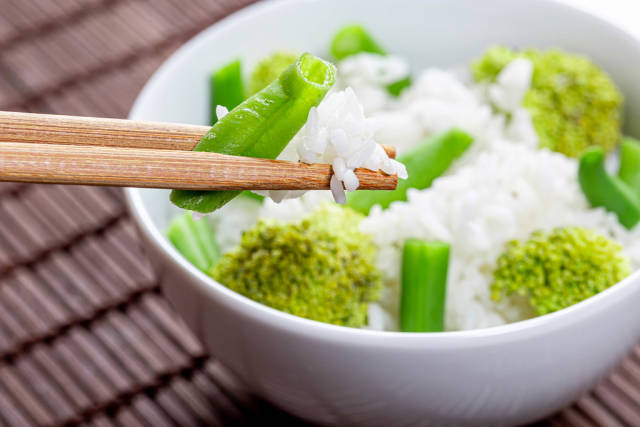 Close up of boiled rice with asparagus and broccoli in a white bowl