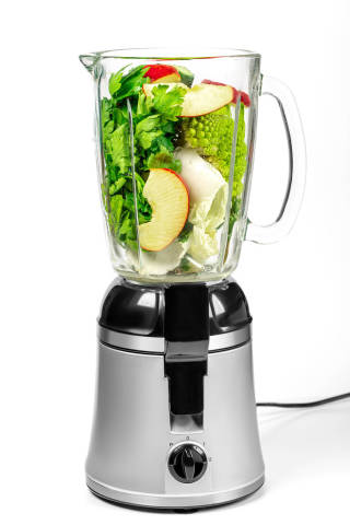 Blender with cabbage, apple slices, cucumber and parsley on a white background