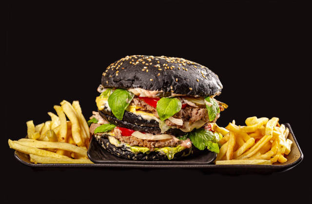 Delicious black Burger and fries on a black tray