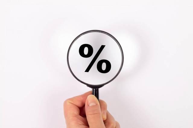 Prozentzeichen in schwarz unter Lupe vor weißem Hintergrund