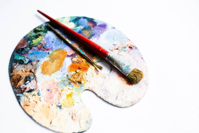Painters palette with oil paint and brushes on white background