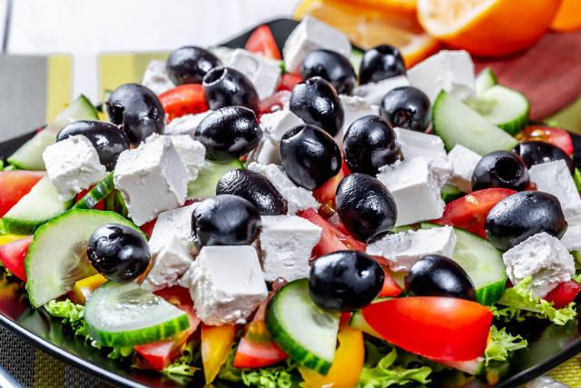 Nahaufnahme griechischer Salat mit schwarzen Oliven, Fetakäsewürfeln, Tomate und Gurke