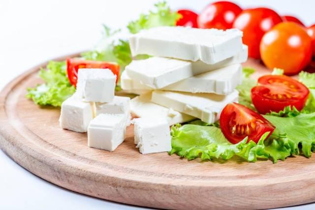 Gewürfelter Fetakäse mit Cherrytomaten und Blattsalat auf hölzernem Küchenbrett