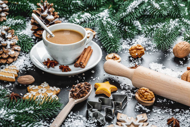 Winter background with ginger biscuits and a cup of coffee. The process of preparing for the holidays