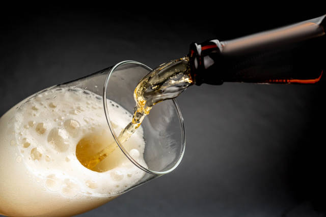 Beer pouring into a glass with foam on a dark background