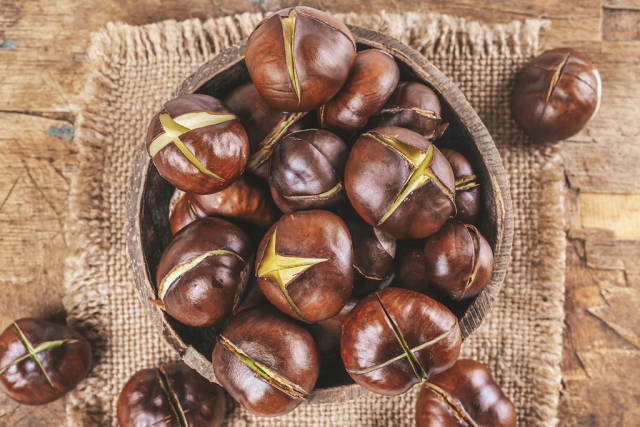 Roasted chestnuts on an old wooden background, top view