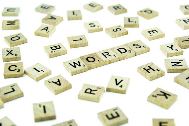 Buchstaben bilden den Schriftzug WORDS zwischen unsortierten Buchstaben-Holzplättchen