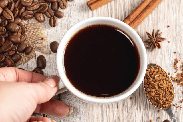 Coffee with cinnamon, anise and grains on wooden background, top view