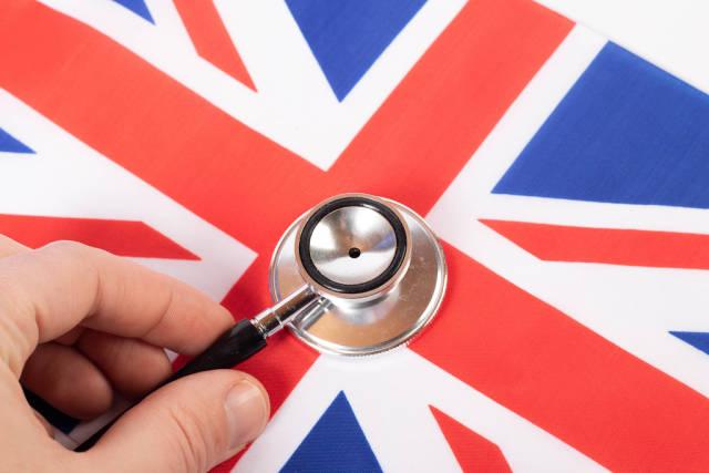 Hand holding stethoscope on British flag