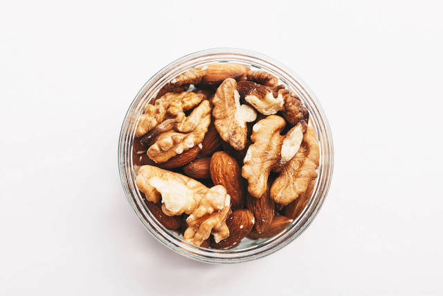 Top view of walnuts and almonds on white background.