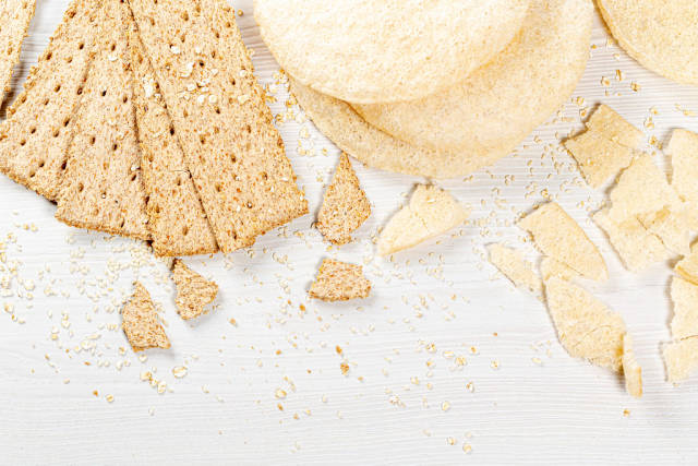 Set of crispy breads with sesame seeds and oatmeal on white background. Top view