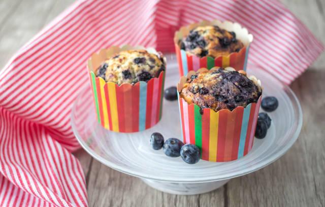 Muffins mit Blaubeeren in Muffinförmchen in Regenbogenfarben