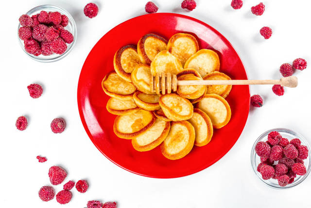 Top view, small pancakes on a red plate with fresh raspberries