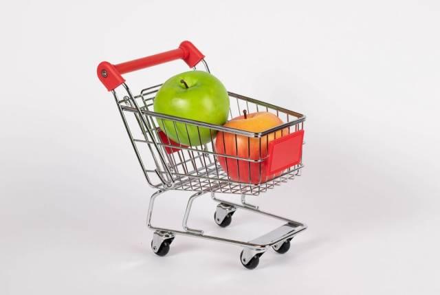 Frische, rote und grüne Äpfel liegen in Einkaufswagen vor weißem Hintergrund
