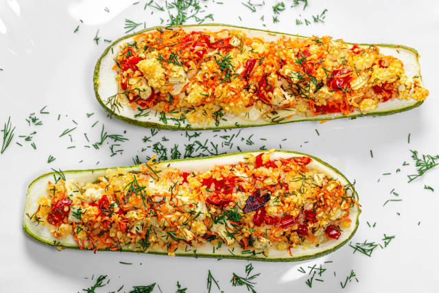 Top view baked zucchini halves with vegetables, couscous and herbs