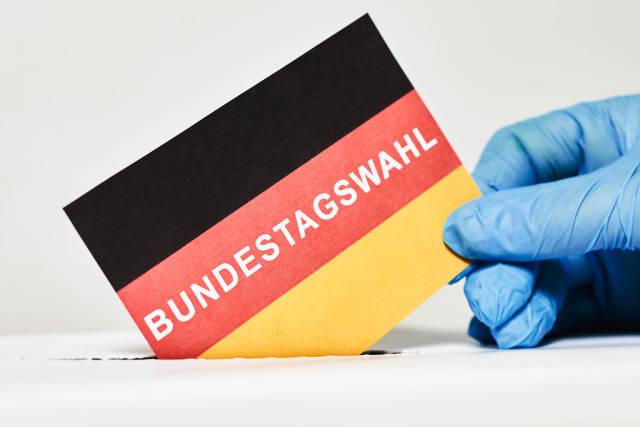 Ein Mann im medizinischen Handschuh, der bei den Bundestagswahlen abstimmt