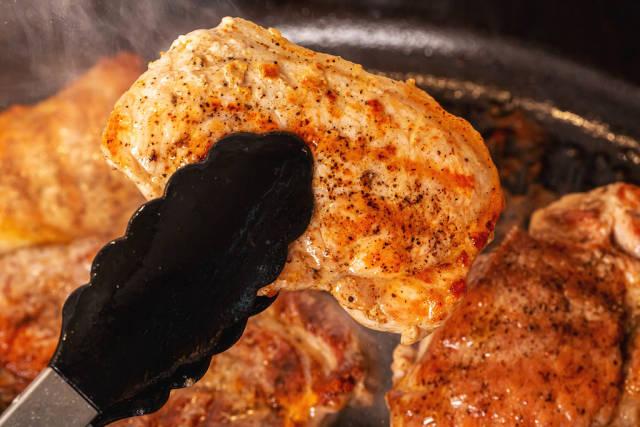 Close-up, fresh hot steak in kitchen tongs