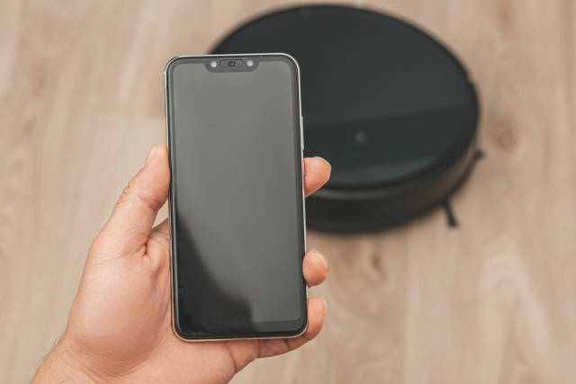 Hand holding smartphone to control the robot vacuum cleaner