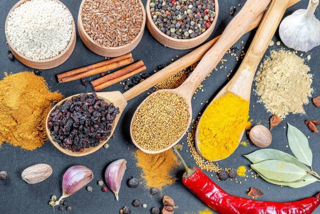 Spices - curry and mustard seeds on wooden spoons with coloured pepper seeds, flax seeds ans sesame in wooden bowls, cinnamon, garlic and nutmeg on black background