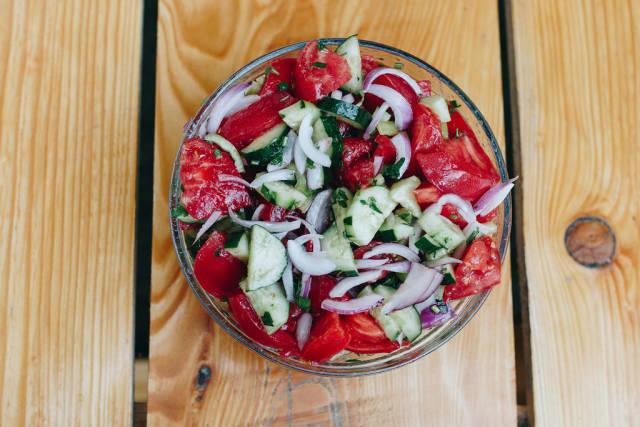 Gesunder Salat mit Tomate, Gurke und Zwiebel von oben fotografiert