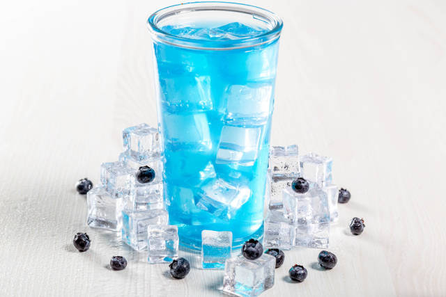 Glass of blue cocktail with ice and fresh blueberries