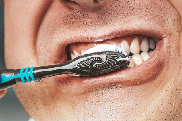 Adult man is cleaning his teeth with brush close up