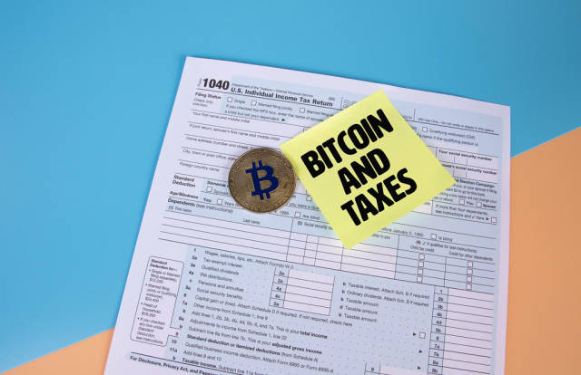 USA tax form 1040 for US individual tax return with golden Bitcoin and sticky note with Bitcoin and Taxes text