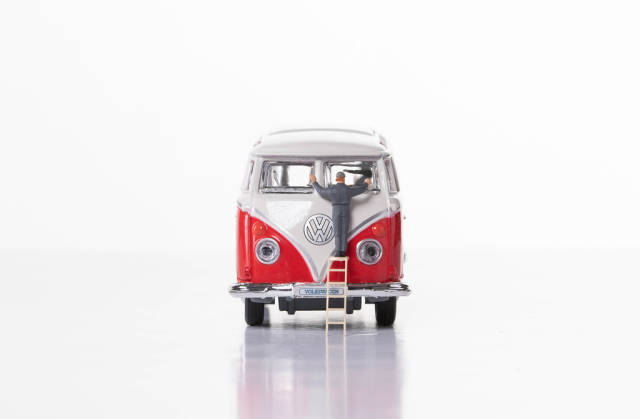 Man cleaning classic VW Camper van on white