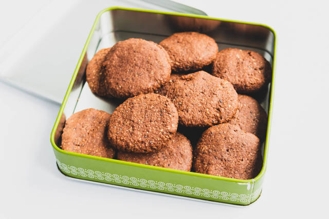 Homemade vegan cocoa cookies in a tin box on white background